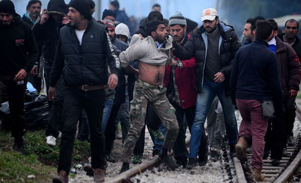 Pakolaiset elävät vaikeissa oloissa Idomenin pakolaisleirillä Pohjois-Kreikassa. Muut raahaavat rikoksesta syyttämäänsä miestä.
