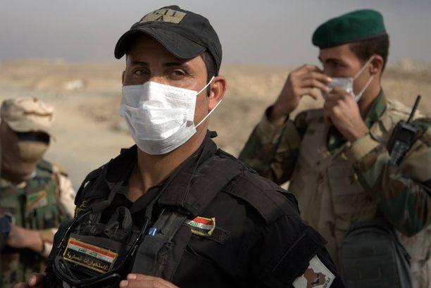 Irakin armeijan sotilaat käyttävät hengityssuojaimia lähellä Awsajan kylää, koska Isis on sytyttänyt öljylähteitä ja rikkitehtaan tuleen.