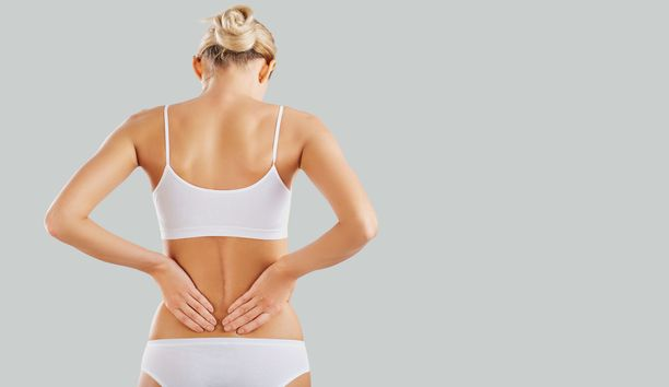 Woman with back pain. Woman in underwear holds her back with her hands. Spinal injury.