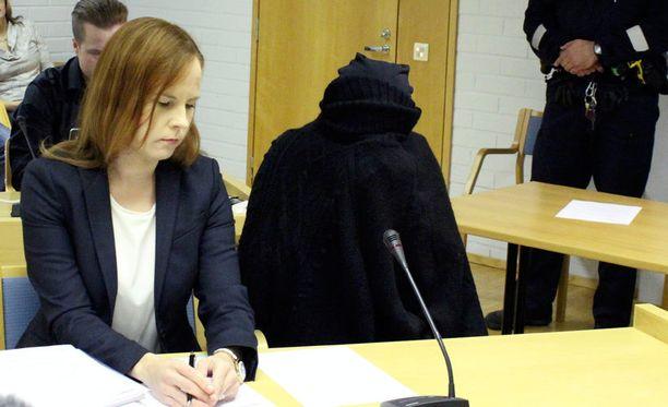Murhista syytetty nainen peitti kasvonsa käräjäoikeudessa.