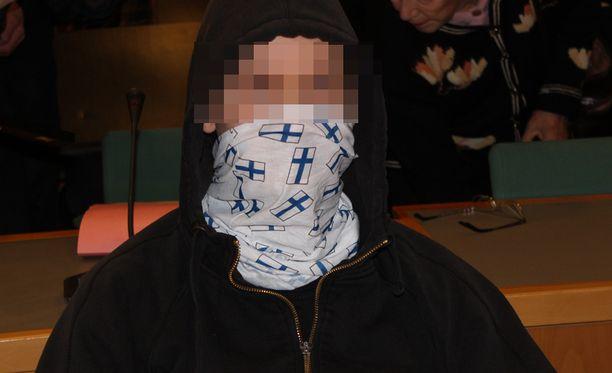 Pitkään poliisia pakoillut syytetty peitti kasvonsa oikeudessa Suomen lipuilla kuvioidulla huivilla.