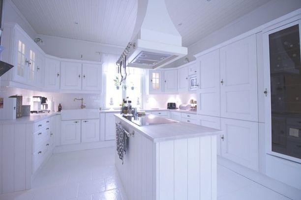 Valkoinen sopii maalaisromanttisiin keittiökaappeihin. Vetimet piristävät ilmettä.