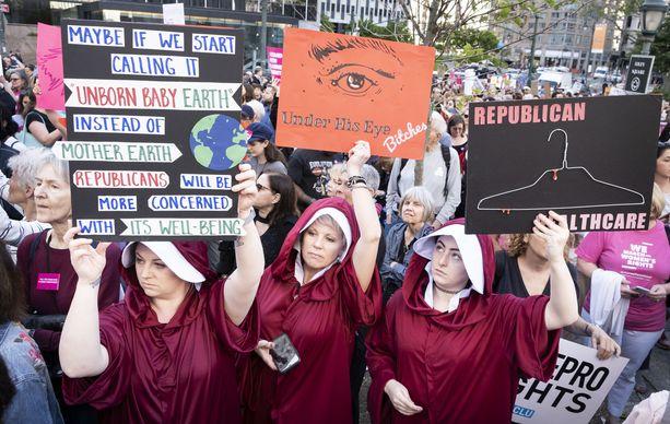 """""""Ehkä jos kutsuisimme sitä """"Syntymättömäksi lapsi maaksi"""" """"Äiti maan"""" sijasta, republikaaneja kiinnostaisi enemmän sen hyvinvointi"""" luki New Yorkissa mielenilmaukseen osallistuneen henkilön kyltissä. Ryhmä oli pukeutunut Handmaid's Tale -sarjasta tuttuihin punaisiin kaapuihin."""