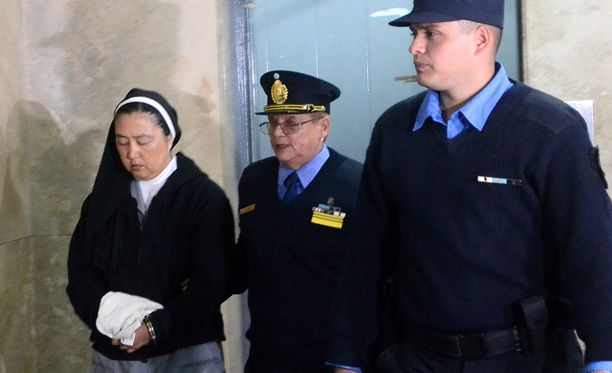 Poliisit saattavat Kosaka Kumikon oikeuden istunnosta.