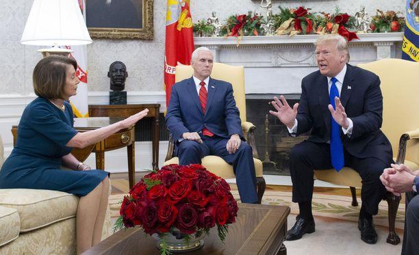 Kuvassa edustajainhuoneen puhemies Nancy Pelosi (vas.), presidentti Trump ja varapresidentti Mike Pence (kesk.) Valkoisessa talossa 11.12.2018.