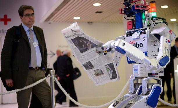 Eteläkorealainen humanoidirobotti pitelee sanomalehteä Maailman talousfoorumin kokouksessa Davosissa 22. tammikuuta.