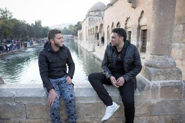 """Serkukset Pbcahim Al-Hassan, 26, ja Abdullah Hassan, 23, istuvat Balikli Gölin, """"Abrahamin altaan"""", reunalla turkkilaisessa Sanliurfan kaupungissa."""