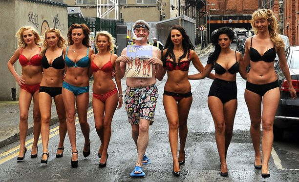 Värikkäistä tempauksista kuuluisa Michael O'Leary poseeraa yhtiönsä lentoemäntien kanssa.