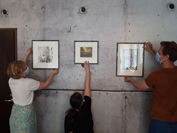 Mira Piitulainen, Anna Kallio ja Petri Haavisto sommittelevat ripustuspaikkoja kehystetyille töille. Taustalla oleva seinäteippaus on Tomas Reganin otos taidekoulun seinästä.