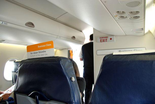 Lentohenkilöstä tarkkailee matkustajia ovella, ja tekee heistä arvioita.
