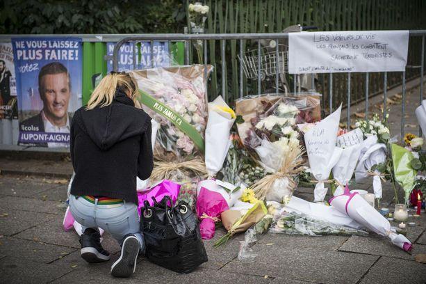 Nuori nainen vei kukkia Pariisin terrori-iskun uhrien muistoksi Bataclanin edustalla marraskuussa 2015.