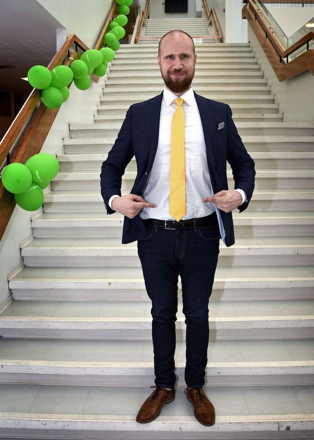 Touko Aalto osoittaa kravatin oikean pituuden.