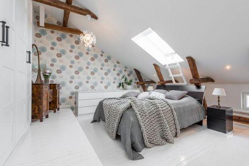Kattoparrut, kattoikkuna ja lautalattia todella tekevät kammarista kodikkaan. Jos niitä ei ole tarjolla, lämmintä tunnelmaa makuuhuoneeseen tuovat vaikkapa kuviollinen tapetti ja muhkea jättineulepeitto.