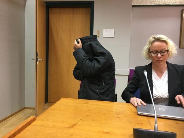 Vangitsemisoikeudenkäyntiin tuotu mies piiloutui takkinsa suojiin.