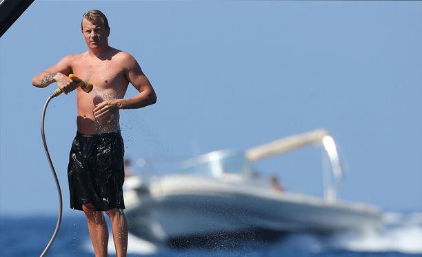 Kimi Räikkönen suihkuttelee veneensä kannella.