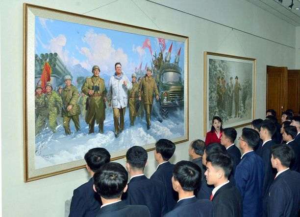 Pohjoiskorealaisia edesmennyttä johtajaa Kim Jong-iliä esittävän maalauksen edessä.