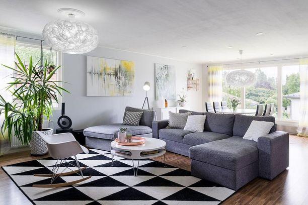 Tässä olohuoneessa värimaailma on toteutettu murretuin sävyin. Valkoista on käytetty huonekaluissa, valaisimissa ja yksityiskohdissa.