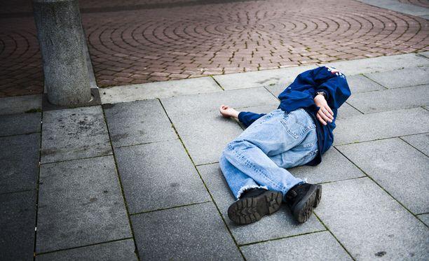 Vakuutusyhtiön kyselyn perusteella puolet suomalaisista kulkee tylysti maassa makaavan, päihtyneeltä vaikuttavan henkilön ohi. Kuvituskuva.