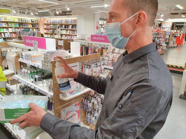 Kauppakeskus Itiksessa olevan Suomalaisen Kirjakaupan myymäläpäällikkö Risto Lehtimäki valmiina asiakaspalveluun. Maskit ja käsidesit ovat hallussa.