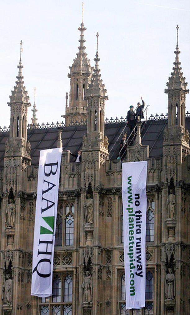 Mielenosoittajat vastustavat Heathrow'n lentokentän laajentamista Britannian parlamenttirakennuksen katolla.