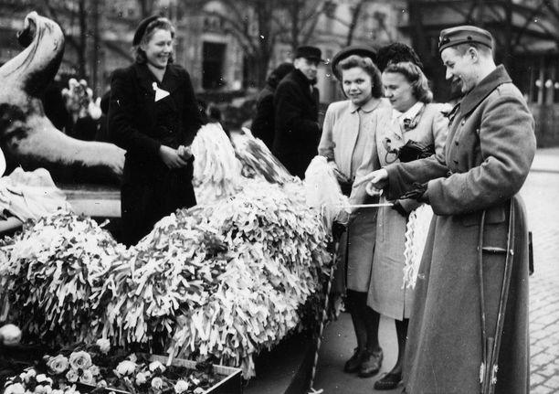 Edes sota-aika ei keskeyttänyt vapun viettoa. Vuodelta 1943 olevassa kuvassa myydään kukkia ja huiskuja Helsingissä vappupäivänä. Kävelykepistä voisi päätellä kuvassa näkyvän nuoren sarkatakkisen miehen haavoittuneen sodassa.