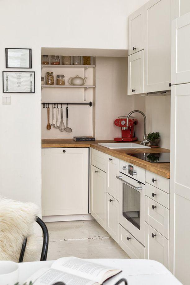 Puutaso tuo lämpöä vaaleaan keittiöön. Kulmaan jäävä seinätila on hyödynnetty fiksusti.