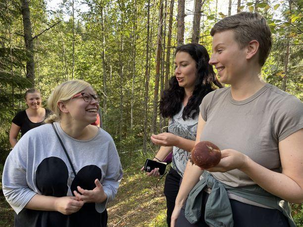 Vihreiden oululainen kansanedustaja Jenni Pitko (oikealla) näyttää poimimaansa tattia espoolaiselle kansanedustajatoverilleen Saara Hyrkölle. Omia luontolöytöjään esittelee eduskuntaryhmän puheenjohtaja Emma Kari (keskellä).