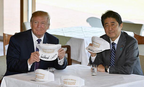 """Shinzo Abe yllätti Donald Trumpin antamalla hänelle lippiksiä, joissa luki vapaasti suomennettuna: """"Tehdään maiden välisistä suhteista entistä tiiviimpiä""""."""