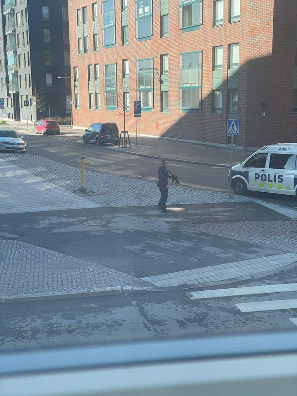 Poliisimies varustautui hälytystehtävälle pitkäpiippuisella aseella.
