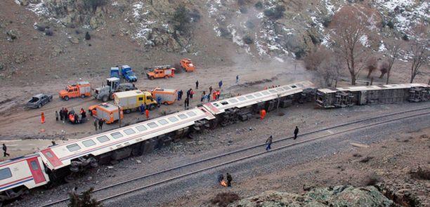 Raiteilta suistunut juna makasi kyljellään raiteiden vieressä.