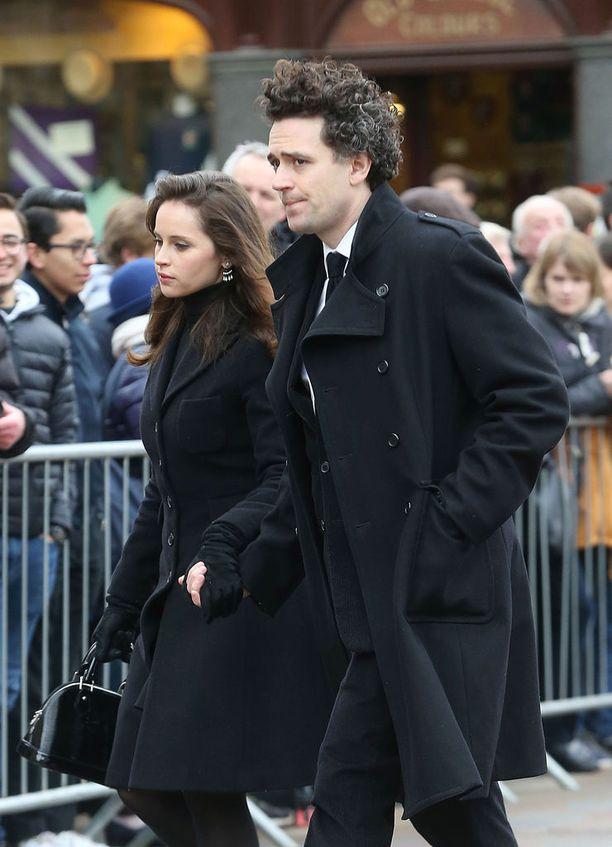 Näyttelijä Felicity Jones saapui hautajaisiin ohjaajamiehensä Charles Guardin kanssa.