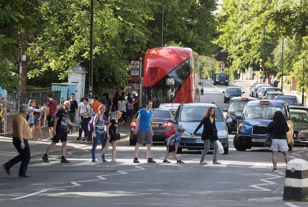 Beatles-fanit ruuhkauttavat liikennettä Abbey Roadilla. Studiota ja sen kuuluisaa jalkakäytävää käy katsomassa päivittäin satoja Beatles-faneja.