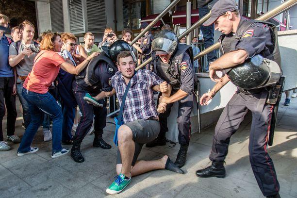 Poliisit pidättämässä miestä mielenosoituksessa Moskovassa sunnuntaina.