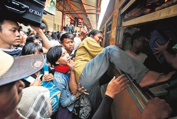 Tehkää tilaa! Tungos oli melkoinen, kun lomanviettoon lähtevät ihmiset änkesivät junaan jopa ikkunoiden kautta Indonesian Jakartassa.