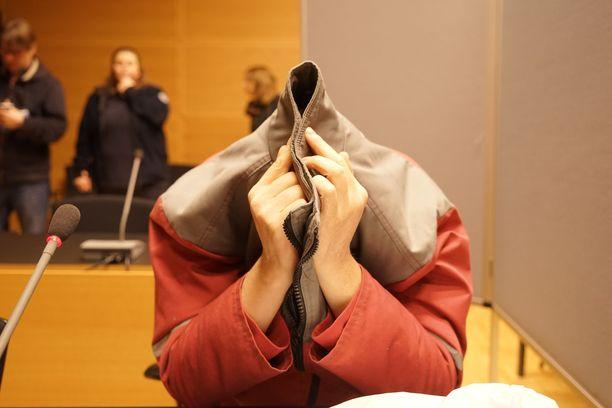 Epäilty peitti kasvonsa takilla.