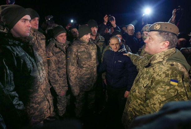 Ukrainan presidentti Petro Poroshenko (oikealla) on esittänyt YK:n rauhanturvaoperaation aloittamista Itä-Ukrainassa. Kuva joulukuulta, jolloin Poroshenko tapasi sotavankeina olleita ukrainalaissotilaita.