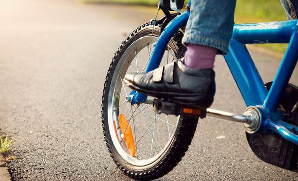 Lapsi kaatui ja loukkaantui auton osuttua pyörään risteyksessä. Kuvituskuva.