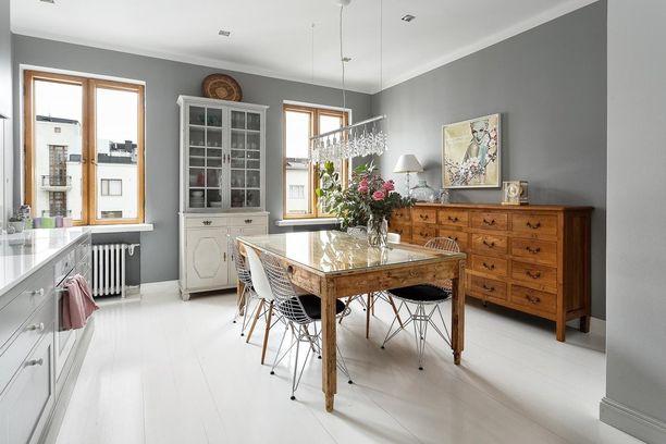 Vanhan, raskasrakenteisen ruokapöydän ilmettä on kevennetty lasitasolla. Modernit design-tuolit ovat tyyliltään täysin erilaiset kuin pöytä - ja siinä se juju piileekin.