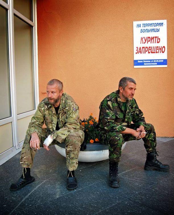 Valkovenäläinen Lev ja ukrainalainen Alexander olivat tiistaina tupakalla Dnipropetrovskissa sijaitsevan sairaalan pääoven edustalla. Takana näkyvä kyltti kieltää tupakoinnin alueella, mutta se ei Ukrainan armeijan vapaaehtoisia sotilaita estellyt.