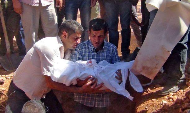 Abdullah Kurdi (kesk.) hautasi poikansa Alanin Syyrian Kobaneen, missä perhe asui.