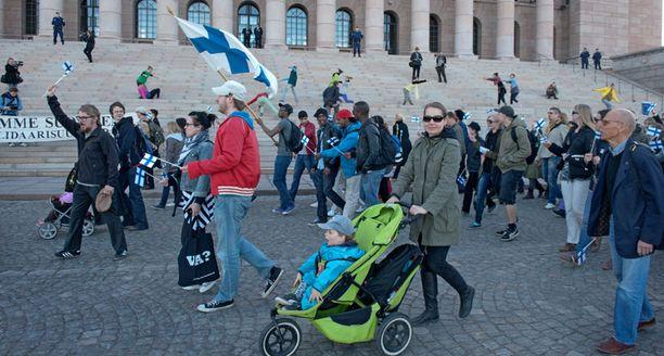 Useilla mielenosoittajilla oli mukanaan Suomen lippu.