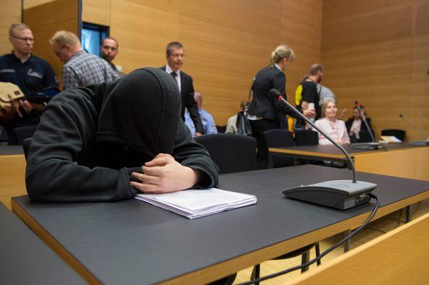 Toinen tuomituista peitti kasvonsa oikeudessa.