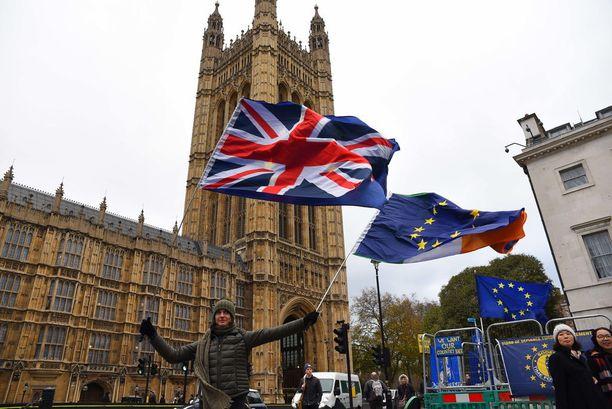Britannian EU-eroa vastustava mielenosoittaja heilutti lippuja parlamenttirakennuksen edustalla Lontoossa keskiviikkona.