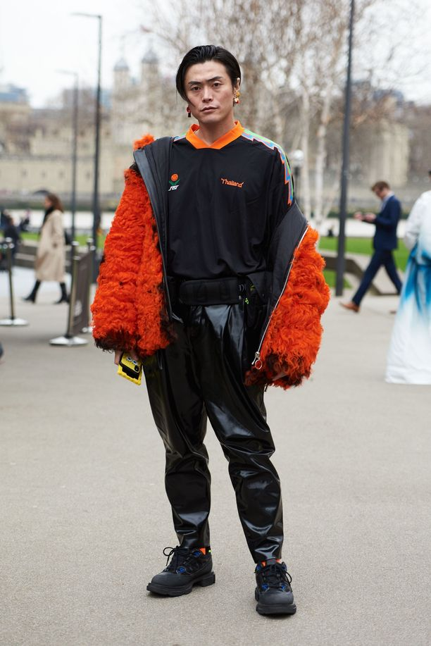 Yu Masuin oranssissa teddytakki ja mustat, kiiltävät nahkahousut ovat sähäkkä kokonaisuus.