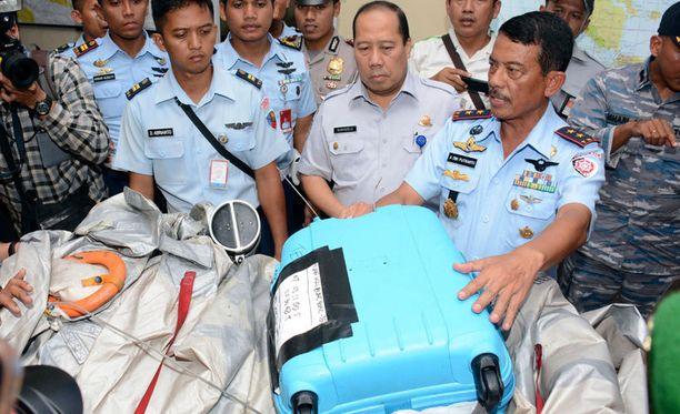 Indonesialaisviranomaiset esittelevät merestä nostettuja matkalaukkuja.