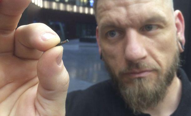 Jowan Österlund esittelee samantyyppistä mikrosirua, jota ruotsalaisfirmat asentavat nyt työntekijöihinsä.