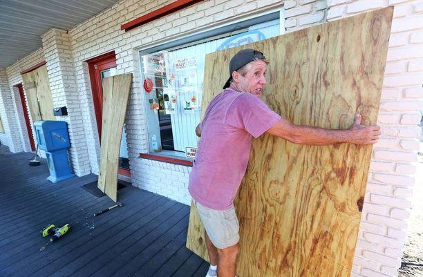Yrittäjä suojasi liikkeensä ikkunoita puulevyillä Floridan Cape Canaveralissa.