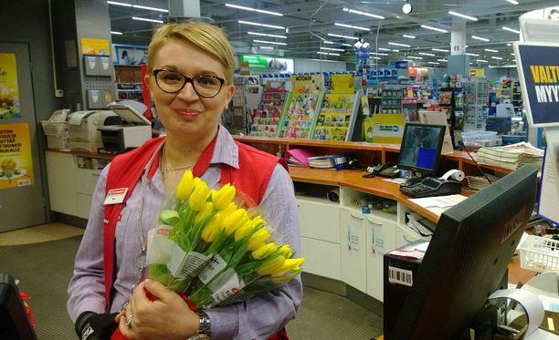 Myyjä Mia Niemi on valmis kukittamaan tuoreen lottovoittajan.