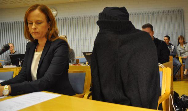 Syytetty saapui oikeudenkäyntiin hunnutettuna.