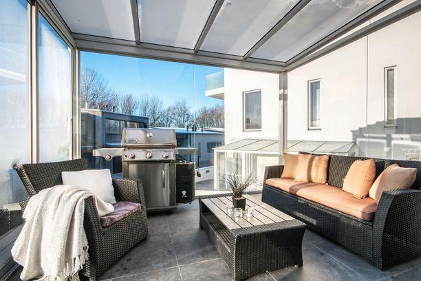 Tässä kelpaisi aloittaa grillikausi. Kodin avarat lasi-ikkunat, parveke ja terassi tulvivat valoa.